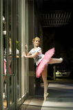 Ballerina dancing in city at night. Color portrait of a beautiful blonde ballerina in white t-shirt and pink tutu dancing in front of a shop window in an urban Stock Photo