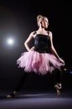Ballerina dancing. In the dark studio Royalty Free Stock Image