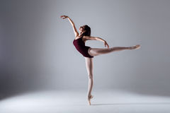 Ballerina dancing in the darkness. Slim ballerina is dancing in the white studio in the contrast light Stock Photo