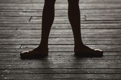 Ballerina dancing feet. Photo of graceful ballerina dancing feet on the floor in backlit stock photos