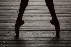 Ballerina dancing feet. Photo of graceful ballerina dancing feet on the floor in backlit stock image