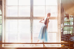 Ballerina is dancing in front of a large window Royalty Free Stock Photo