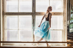 Ballerina is dancing in front of a large window Stock Photo