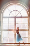 Ballerina is dancing in front of a large window Royalty Free Stock Photography