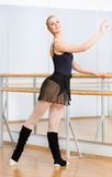 Ballerina dancing near barre in studio Stock Image
