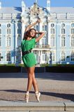 Ballerina is dancing near the palace. Beautiful ballerina is dancing outside with palace background Royalty Free Stock Photography