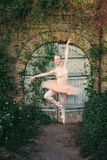 Ballerina dancing outdoors classic ballet poses in urban backgro Royalty Free Stock Image