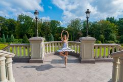 Ballerina dancing at park, standing in pointe position. Outdoors, spring Stock Photos