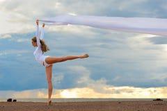 Ballerina dancing at the sea beach. Royalty Free Stock Image