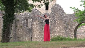 Ballerina dancing on the street. Against the backdrop of an old ruined castle stock video