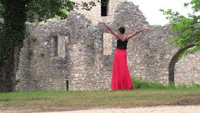 Ballerina dancing on the street. Against the backdrop of an old ruined castle stock video footage