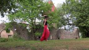 Ballerina dancing on the street. Against the backdrop of an old ruined castle stock footage