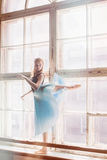Ballerina dancing at window sill background. Girl in a turquoise ballet skirt royalty free stock photography