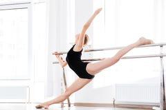 Ballerina della donna che allunga vicino al bastone sulla parete nello studio di ballo Fotografia Stock Libera da Diritti