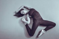 Ballerina della giovane donna che si trova e che allunga sul pavimento allo studio di balletto, vista da sopra Rebecca 36 Immagine Stock