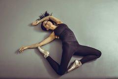 Ballerina della giovane donna che si trova sul pavimento senza sensibilità allo studio di balletto, vista da sopra Fotografia Stock