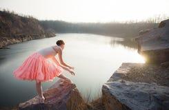 Ballerina in der Balletthaltung über dem See stockfotografie