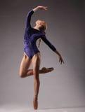 Ballerina in der blauen Ausstattung, die auf Zehen, Atelieraufnahme, oben schauend aufwirft Lizenzfreies Stockfoto