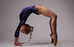 Ballerina in der blauen Ausstattung, die in Brückenposition aufwirft Schönes Tanzen der jungen Frau der Paare Lizenzfreie Stockbilder