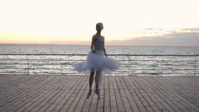 Ballerina di dancing in tutu bianco e pointe sull'argine sopra la spiaggia del mare o dell'oceano ad alba Giovane bella donna video d archivio