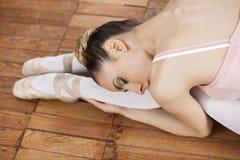 Ballerina, die auf Bretterboden am Studio verbiegt Lizenzfreies Stockfoto