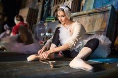 Ballerina, die auf der Aufwärmenbühne hinter dem vorhang sitzt Stockfotos