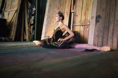 Ballerina, die auf der Aufwärmenbühne hinter dem vorhang sitzt lizenzfreies stockbild