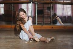 Ballerina, die auf ihre Ballettschuhe sich setzt Stockfoto