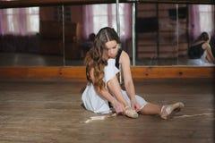Ballerina, die auf ihre Ballettschuhe sich setzt Lizenzfreies Stockbild