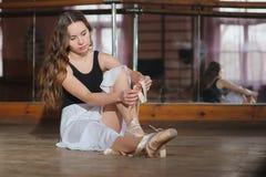 Ballerina, die auf ihre Ballettschuhe sich setzt Stockbild