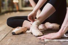 Ballerina, die auf ihre Ballettschuhe sich setzt Stockbilder