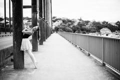 Ballerina, die an der Brückensäule sich lehnt Stockfotografie