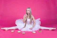 Ballerina, die eine Spalte im Ballettröckchenrock isst einen Donut tut Lizenzfreies Stockbild