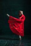 Ballerina, die in pointe Schuhen am schwarzen hölzernen Pavillon aufwirft Stockbilder