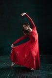 Ballerina, die in pointe Schuhen am schwarzen hölzernen Pavillon aufwirft Stockfoto