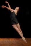 Ballerina, die in Studio auf schwarzem Hintergrund springt Lizenzfreies Stockbild