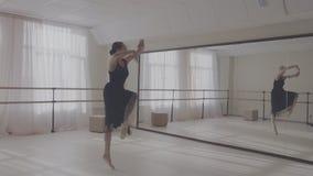 Ballerina die in studio voor spiegel dansen stock video