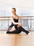 Ballerina does exercises sitting on the wooden floor Stock Photos