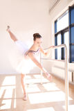 Ballerina Doing Barre Exercises in Sunny Studio Royalty Free Stock Photography