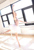 Ballerina Doing Barre Exercises in Sunny Studio Stock Photos