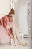 Ballerina dress pointes. Pretty young ballerina puts on pointe. Home training Stock Photo