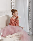 Ballerina drink coffee. Pretty young ballerina drinking coffee sitting on a chair. Ballerina in tutu and pink sweater Stock Photos