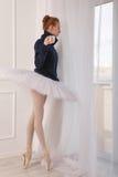 Ballerina drinking black tea at the window Stock Images