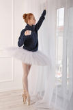 Ballerina drinking black tea by the window. Pretty young ballerina drink black tea by the window. A girl wearing a tutu and black sweater Royalty Free Stock Photos