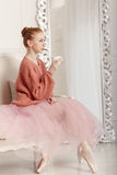 Ballerina drinking tea. Pretty young ballerina tea drinkers. Ballerina in tutu and pink sweater Stock Image