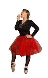 Ballerina eats cake. Attractive woman in black-red ballerina dress eats cake on isolated white background Stock Photography