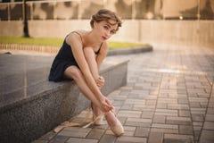 Ballerina esile nei blackdress che mettono sulle scarpe del pointe esterno Fotografie Stock Libere da Diritti