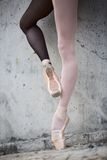 Ballerina feet close-up on a background of. Photo of the young graceful ballerina feet close-up on a background of textured concrete wall. Legs dressed in stock images