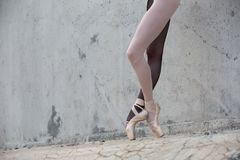 Ballerina feet close-up on a background of. Photo of the young graceful ballerina feet close-up on a background of textured concrete wall. Legs dressed in stock photos