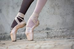 Ballerina feet close-up on a background of. Photo of the young graceful ballerina feet close-up on a background of textured concrete wall. Legs dressed in royalty free stock photos